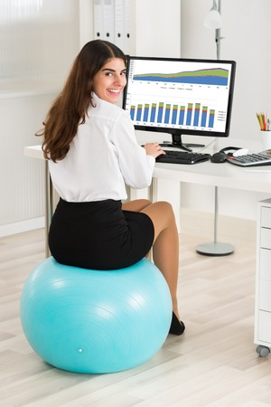 51726192 Portrait Of Hy Young Businesswoman Using Computer While Sitting On Exercise Ball In Office